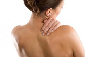 Frau mit freiem Oberkörper von hinten. Hält sich Hand rechts an Hals/Nacken. Gesicht nach rechts
